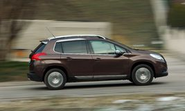 Moving small brown car Royalty Free Stock Image