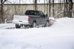 Moving snow job. A truck with a snow plow does his job early, to move the heavy messy white snow Royalty Free Stock Photos