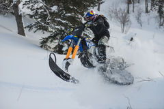 Moving snowmobile in winter forest in the mountains Stock Photo