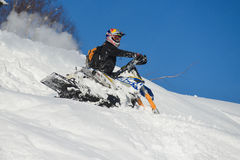 Moving snowmobile in winter forest in the mountains Stock Photography