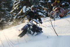 Moving snowmobile in winter forest in the mountains Royalty Free Stock Photography