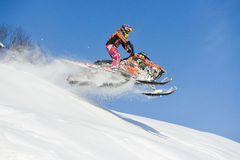 Moving snowmobile in winter forest in the mountains Royalty Free Stock Photos