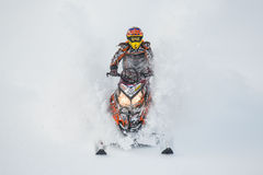 Moving snowmobile in winter forest in the mountains Royalty Free Stock Photo