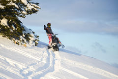 Moving snowmobile in winter forest in the mountains. SAKHALIN RUSSIAN - JANUARY 23 : Oleg Bibikov moving snowmobile in winter forest in the mountains of Sakhalin Stock Images