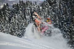 Moving snowmobile in winter forest in the mountains Stock Photos