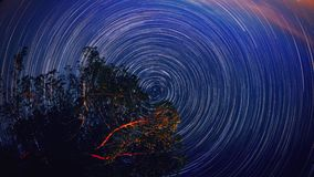 Moving star trails in night sky circular Timelapse. The Milky Way galaxy rotating over the tree range in summer time UHD