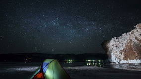 Moving stars above tent at night time lapse stock video footage