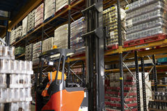 Moving stock in distribution warehouse with an aisle truck Stock Images