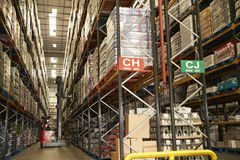 Moving stock in a distribution warehouse with an aisle truck Royalty Free Stock Photography