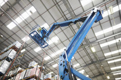 Moving stock in a warehouse with a cherry picker, low angle stock photos