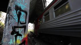 Moving suburban electric train under bridge moves on camera. Graffiti. Moving suburban electric train under bridge moves on camera. Summer day. One bicycle stay stock video footage