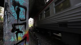 Moving suburban electric train uner bridge. Summer day. Bicycle  left. Graffiti. Moving suburban electric train uner bridge. Summer day. One bicycle stay on left stock footage