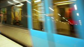 Moving subway train. Underground train departs from modern subway station. Wagons with people following its route