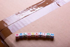 Moving to another office or house. Word relocation. On a cardboard box with a sealed tape Royalty Free Stock Image