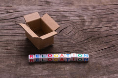 Moving to another office or house. Word relocation. On an old wooden background royalty free stock images