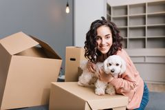 Moving to new apartment of young pretty woman with little dog. Chilling on bed surround carton boxes with pet, smiling. To camera, expressing positivity stock photography