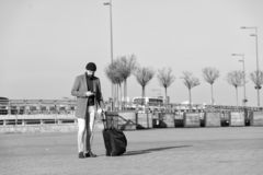 Moving to new city alone. Man bearded hipster travel with luggage bag on wheels. Traveler with suitcase arrive airport. Railway station urban background stock image