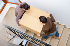 Moving to new home. Two young women carrying up cardboard box on stariway to new home Stock Photo