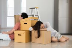 Tired Asian couple sleep at moving boxes stock photo