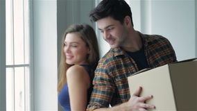 Moving to a new life. A girl and a guy holding boxes for moving the hands and looking at each other while a couple in love standing at the window among boxes stock footage