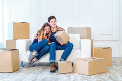 Moving to a new life. A girl and a guy holding boxes for moving Royalty Free Stock Image