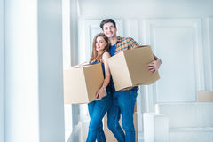 Moving to a new life. A girl and a guy holding boxes for moving Royalty Free Stock Photos