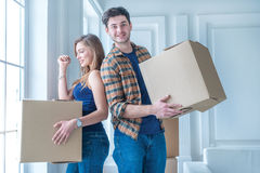 Moving to a new life. A girl and a guy holding boxes for moving Royalty Free Stock Images