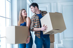 Moving to a new life. A girl and a guy holding boxes for moving Royalty Free Stock Photography