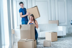 Moving to a new life. A girl and a guy holding boxes for moving Stock Images