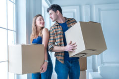 Moving to a new life. A girl and a guy holding boxes for moving. The hands and smiling at the camera while a couple in love standing at the window among boxes Royalty Free Stock Photo