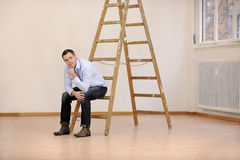 Moving to new office or house. Man sitting on ladder in empty room stock photo