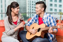After moving together young man plays love song for his girlfrie Stock Images