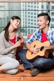 After moving together young man plays love song for his girlfrie Royalty Free Stock Photography