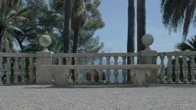 Moving towards luxurious marble bench under palm trees stock video footage