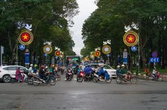 Moving traffic crossing the street during rush hour in HCMC in Vietnam. Ho Chi Minh City, Vietnam - August 23, 2017: Moving traffic crossing the street during stock photography