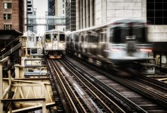 Moving Train on elevated tracks within buildings at the Loop, Glass and Steel bridge between buildings - Chicago City Center - Lon. G Exposure, Bleach Bypass Royalty Free Stock Images