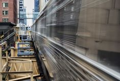 Moving Train on elevated tracks within buildings at the Loop, Glass and Steel bridge between buildings - Chicago City Center - Lon. G Exposure - Chicago Stock Photos