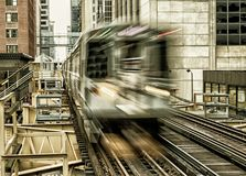 Moving Train on elevated tracks within buildings at the Loop, Glass and Steel bridge between buildings - Chicago City Center. Long Exposure, Black Gold Stock Images