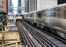 Moving Train on elevated tracks within buildings at the Loop, Glass and Steel bridge between buildings - Chicago City Center - Lon. G Exposure - Chicago Royalty Free Stock Photos