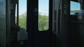 Moving train inside. Outside, a bright sun and landscapes, inside is dark stock video footage