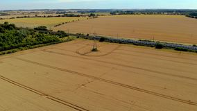London train. Moving train from London in the wheat fields, in summer time stock video footage