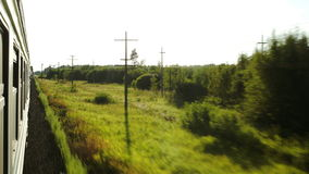 Moving train and passing landscape. Side view of a moving train along with passing summer landscape stock footage