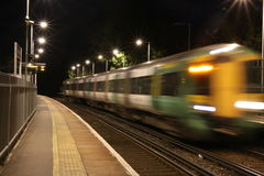 Moving train passing through station at night Stock Photos