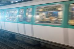 Moving train passing a station platform. Moving illuminated carriage of a passenger train passing a station platform with reflections of the lights on the Stock Images
