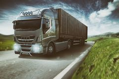 Grey truck moving fast on the road in a natural landscape with cloudy sky royalty free stock photography