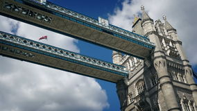 Moving under tower bridge with flag blowing stock footage