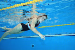 Moving underwater. Underwater picture of a young woman swimming Stock Image