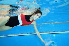 Moving underwater. Underwater picture of a young woman swimming Royalty Free Stock Photography