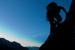 Moving up. Silhouette of a climber with large copay space Stock Images