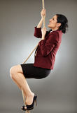 Moving up in career. Latin businesswoman climbing on a rope, conceptual image of career achievement Stock Image
